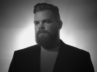 Com Truise Wearing A Suit And Tie Looking At The Camera