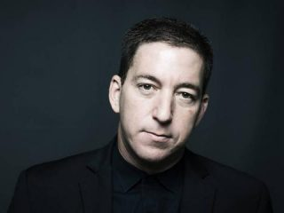 Glenn Greenwald Wearing A Suit And Tie Smiling And Looking At The Camera