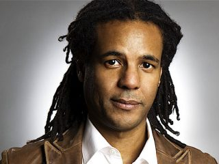 Colson Whitehead Wearing A Suit And Tie Smiling And Looking At The Camera
