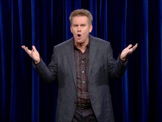 Brian Regan In A Suit Standing In Front Of A Curtain