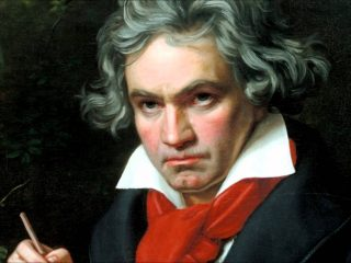 Ludwig Van Beethoven Wearing A Red Jacket Is Looking At The Camera