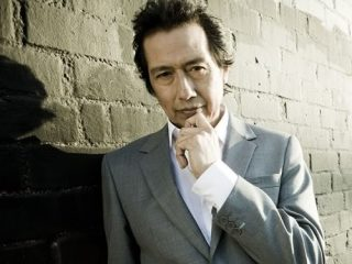 Alejandro Escovedo In A Suit Standing In Front Of A Brick Building