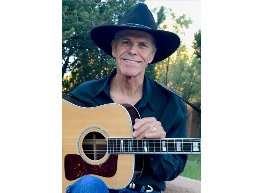A Man Wearing A Hat And Holding A Guitar