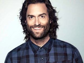 Chris D'Elia Wearing A Striped Shirt And Looking At The Camera